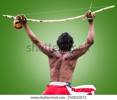 Brazilian performing Capoeira with Berimbau Instrument on green background - stock photo