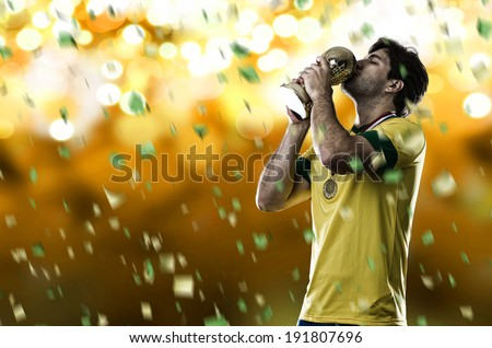 Brazilian soccer player, celebrating the championship with a trophy in his hand, on a yellow background. - stock photo