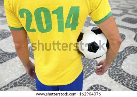 Brazilian soccer player holding football wears 2014 shirt in Brazil colors Rio de Janeiro - stock photo