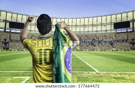 Brazilian soccer player holding the flag of Brazil celebrates with the fans on the stadium - stock photo