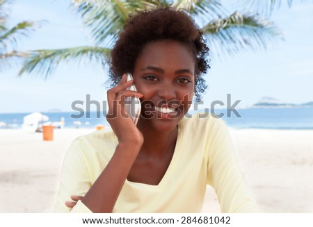 Brazilian woman at beach laughing at phone - stock photo
