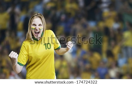Brazilian woman celebrates on the stadium with her face painted - stock photo