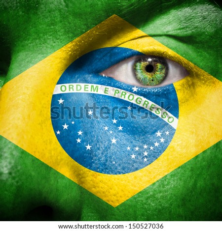 Brazillian flag painted on a man's face to support his country Brazil - stock photo