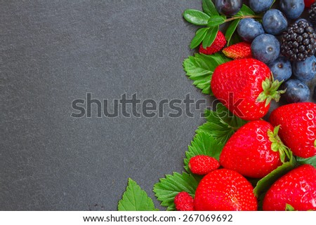 brder  of fresh  wild berries and  leaves with copy space  on black stone background - stock photo
