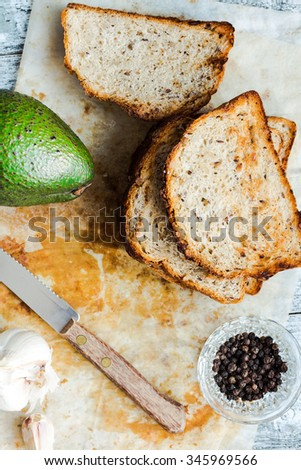 bread and a whole avocado with pepper and garlic, a set of products to toast - stock photo