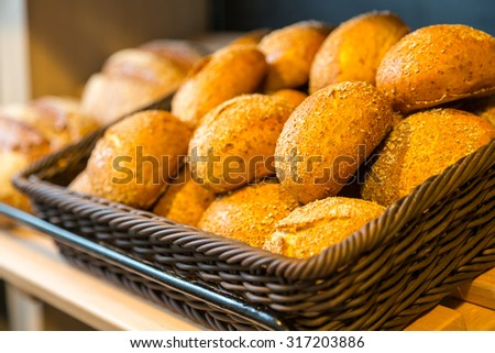 Bread and buns in baskets on shelf in bakery or baker's shop - stock photo