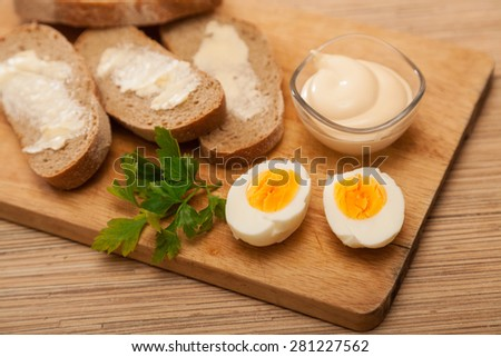 bread and butter, egg, greens and mayonnaise on a wooden board
