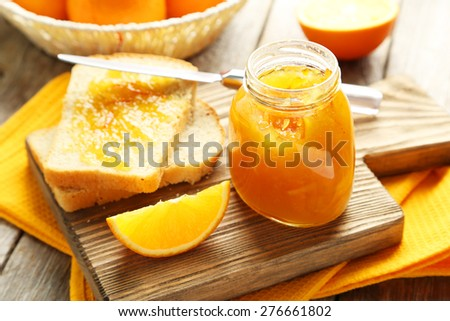 Bread and orange jam on grey wooden background - stock photo