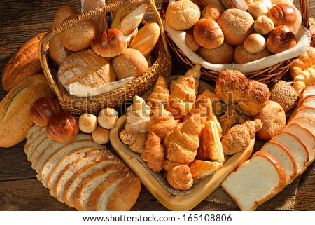 Bread and rolls in wicker basket on old wooden background.  - stock photo