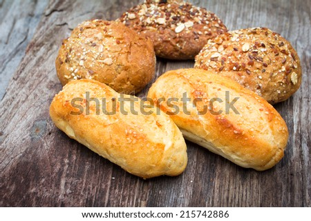 bread and rolls on old wood background
