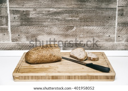 Bread and slices/Whole wheat bread with crispy sesame seeds set on a wooden trencher with two cut slices and a bread knife in a kitchen interior. - stock photo