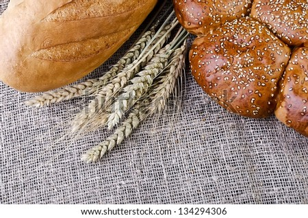 Bread and wheat ears close-up, lying on sacking