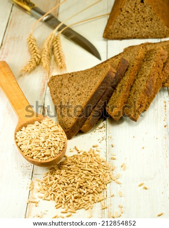 bread and wheat in a spoon on the wooden table