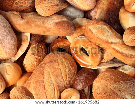 Bread background staple food concept with a group of baked goods from a bakery or home cooking made from whole wheat and grains with breads as pumpernickel pita focaccia bagel made from dough. - stock photo