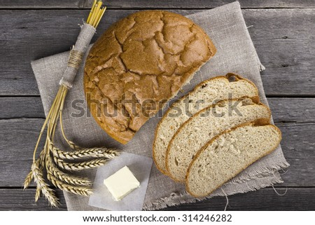 Bread, butter, wheaten ears on a wooden background. Top view