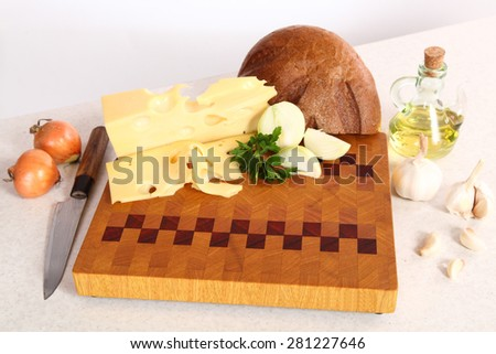 Bread, cheese, vegetables on a chopping board and vegetable oil - stock photo