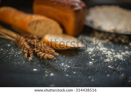 Bread composition with wheats. Very shallow DOF photo and specific art curly bokeh for extra volume. - stock photo