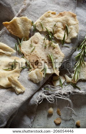 Bread crisp with rosmary on rustic backgroun with jute napkin - stock photo