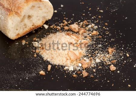 bread crumbs on black  - stock photo