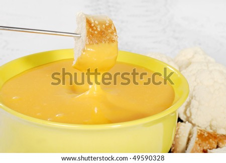 bread dipped in cheese fondue - stock photo