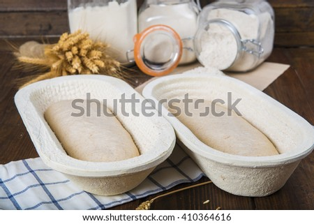 Bread dough leavening in the fermentation basket on the bakery table - stock photo