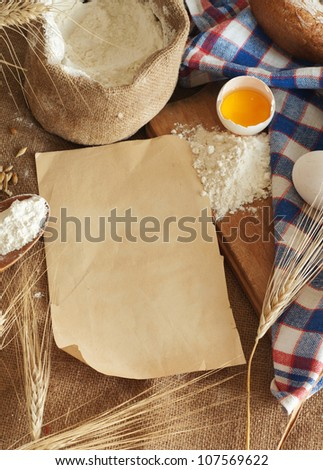 bread, eggs and flour a sheet of paper for the recipe - stock photo
