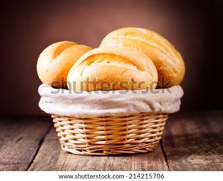 bread in wicker basket on wooden background - stock photo