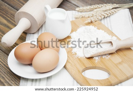 Bread Ingredients - flour, eggs,wheat and milk on a wooden background