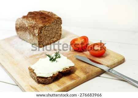 Bread lice with cream cheese and tomatoes on wood cutter on bright white table and white background - stock photo