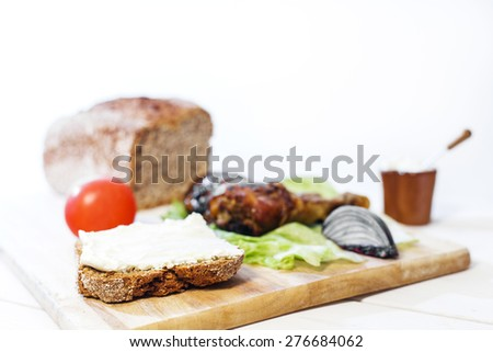 Bread lice with cream cheese, onions, oven cooked chicken leg and tomatoes on wood cutter on bright white table and white background - stock photo