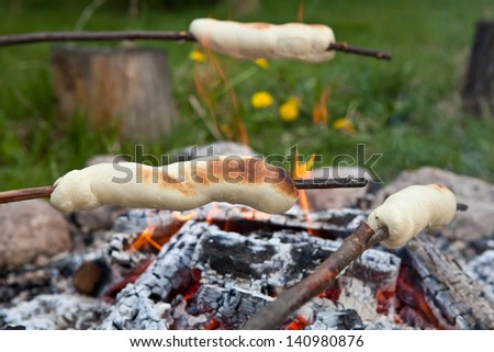 bread on a stick over a fire on long twigs until they are a saft flufy golden brown - stock photo