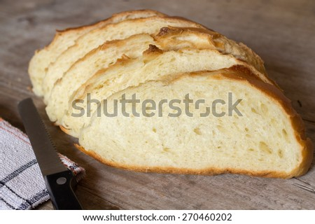 Bread slice with bread knife on wooden background - stock photo