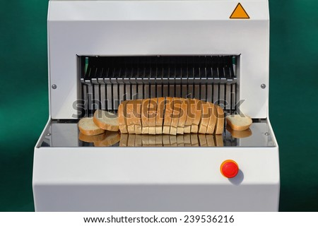 Bread slicer with big loaf in bakery - stock photo