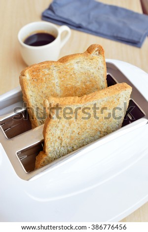 Bread slices in toaster with coffee - stock photo