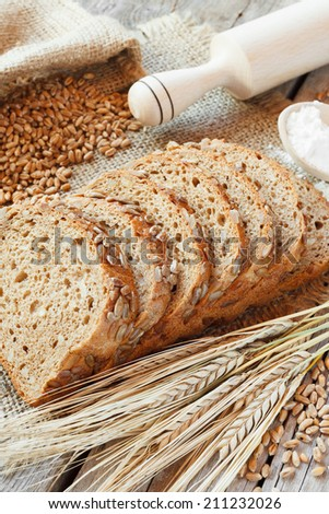 bread slices, rolling pin, grain and rye ears on kitchen table