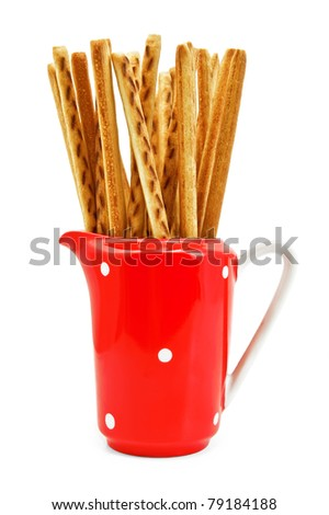 Bread sticks in red milkman isolated on a white background - stock photo