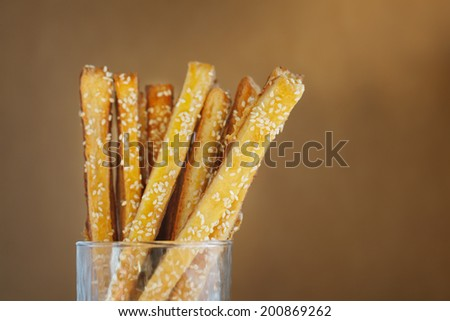 Bread sticks  with cheese and sesame in the glass, cose up - stock photo
