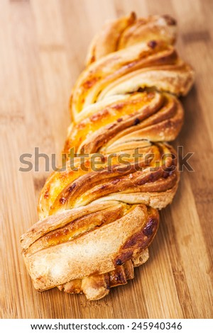 Bread twirl in the basket on a wooden table. - stock photo