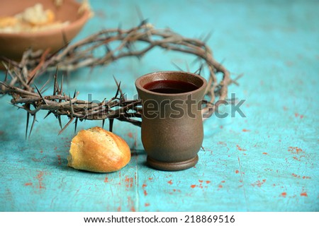 Bread, wine and crown of thorns on vintage table - stock photo