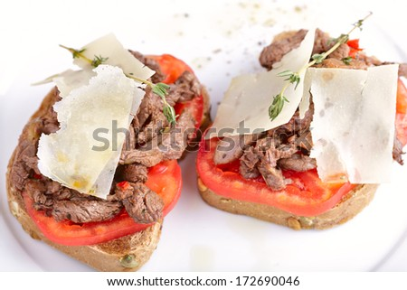 Bread with beef, tomato and parmesan - stock photo