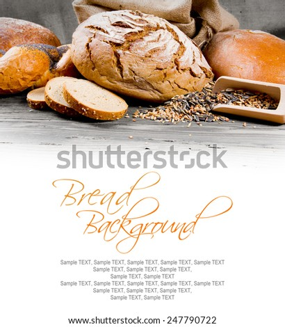 Bread with buns, seeds and slices on wooden background with white space for text - stock photo