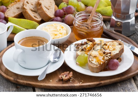 bread with butter, honey, nuts and grapes for breakfast, horizontal - stock photo