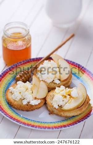 Bread with cottage cheese or ricotta, honey and apple on plate on wooden background. Selective focus. Healthy eating. - stock photo
