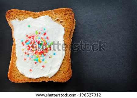 Bread with fresh cheese and colored sprinkles on black paper