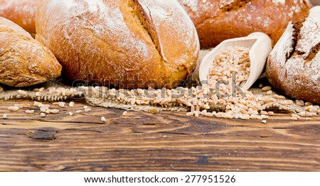 Bread with rolls and seeds on burlap and wooden background