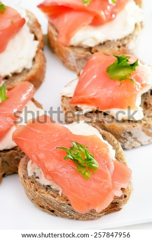 Bread with salmon on white plate, close up view - stock photo