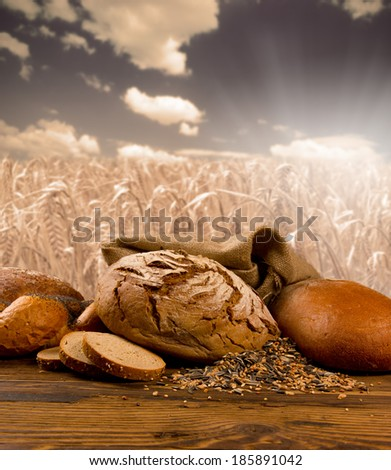 Bread with slices and buns on wooden background