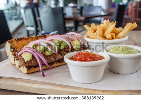 Bread with spicy pork sausage, avocado, tomato, white cheese and fries.