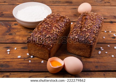 Bread with sunflower seedson the wooden table - stock photo