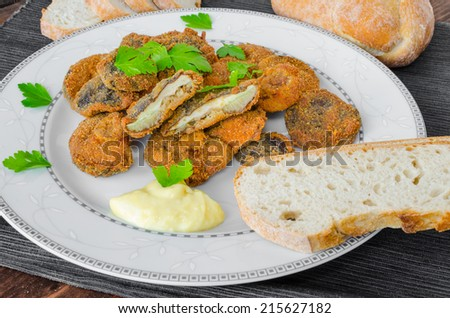 Breaded and fried mushrooms with homemade mayonnaise, fresh herbs - stock photo